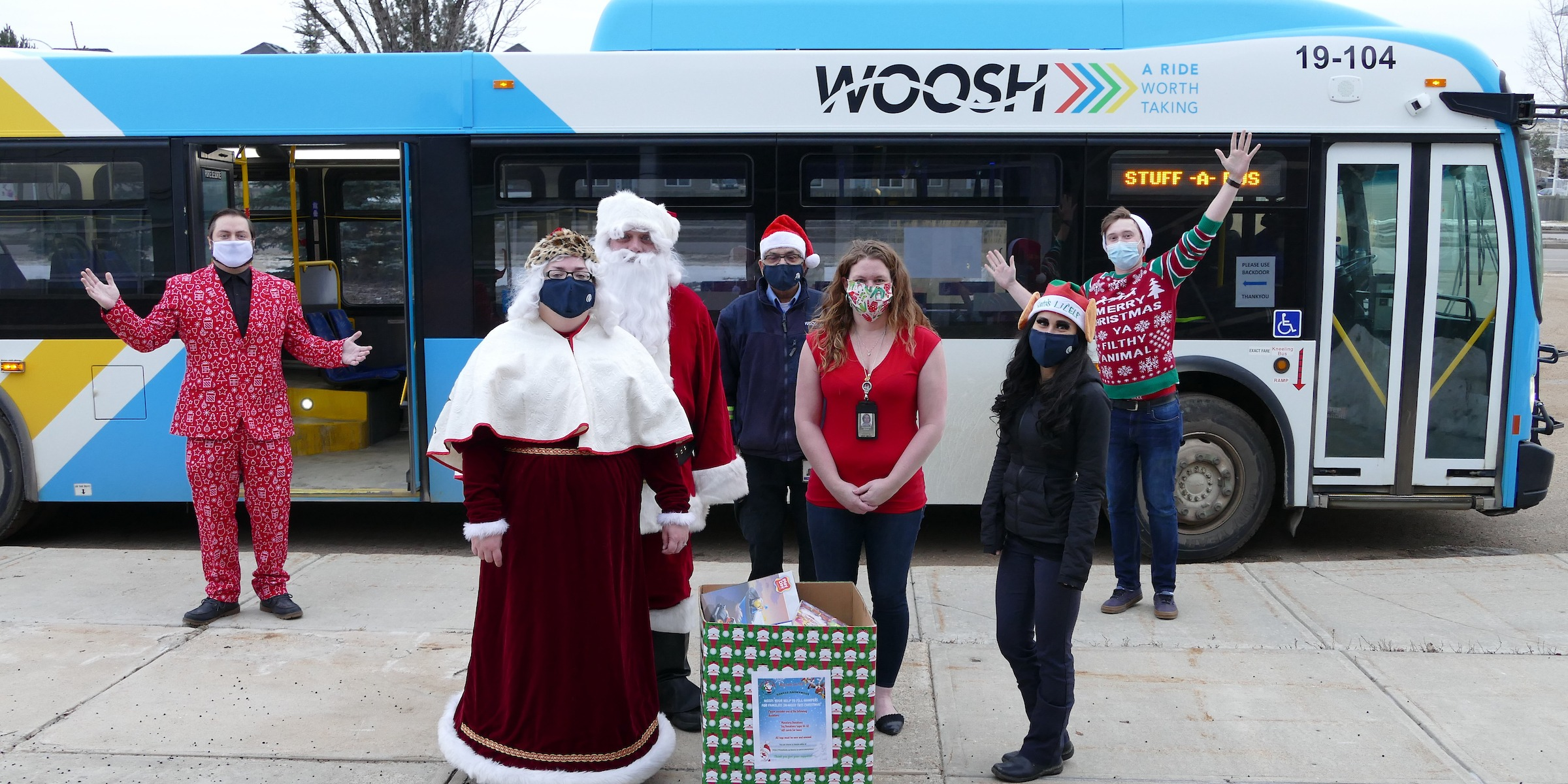 Santa, Mrs. Claus and their helpers pose beside a transit bus